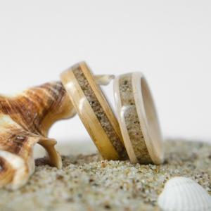 Męska kremowe zebrano, damska dąb bielony - obie inkrustowane pięknym pisakiem Bałtyku. Dla miłośników morza.